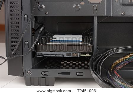 Internal hard drive inserted in computer case.