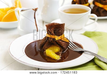 Chocolate pancakes with orange and chocolate sauce