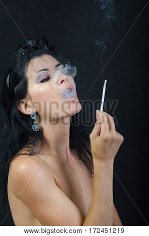 a woman holds a cigarette in a hand