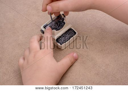 Hand Holding Retro Syled Tiny Typewriter Model