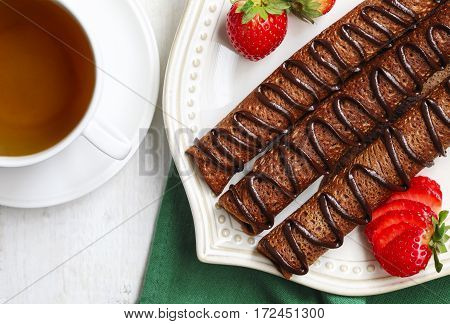 Chocolate crepes and cup of tea close up