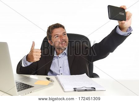 young attractive and happy businessman in suit working at office laptop computer desk using mobile phone for taking selfie photo posing having fun giving thumb up isolated on white background