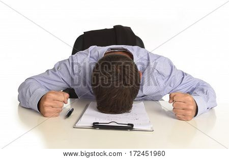 desperate stressed businessman sitting at office desk with hands on his head crying devastated and frustrated in overwork and business crisis concept isolated on white background