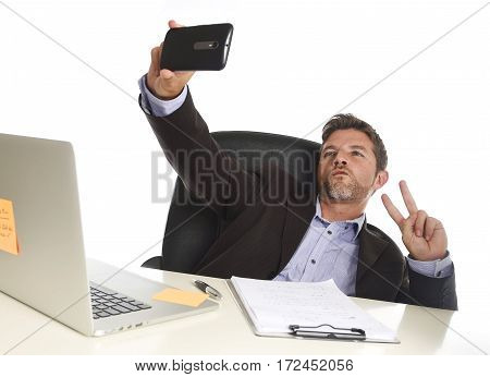young attractive and happy businessman in suit working at office laptop computer desk using mobile phone for taking selfie photo posing having fun isolated on white background