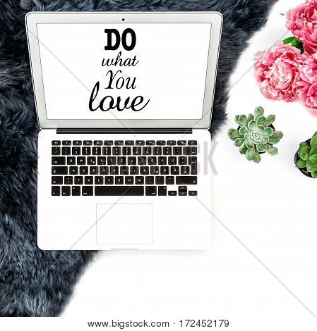 Workplace Laptop with white screen succulent flowers fur background. Flat lay mock up. Sample text Do What You Love