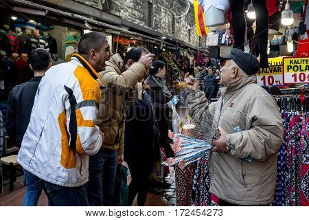 ISTANBUL TURKEY - DECEMBER 28 2015: Old merchant trying to sell anti stress head massage devices to laughing men near the spice bazaar on the European side of the city
