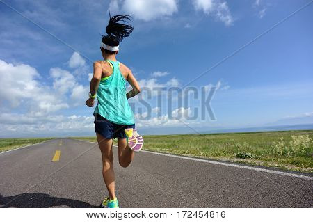 young fitness woman trail runner running on road