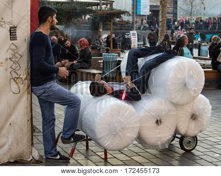 ISTANBUL TURKEY - DECEMBER 28 2015: Young delivery boys having a rest on their parcel in Eminonu district on the European side of the city