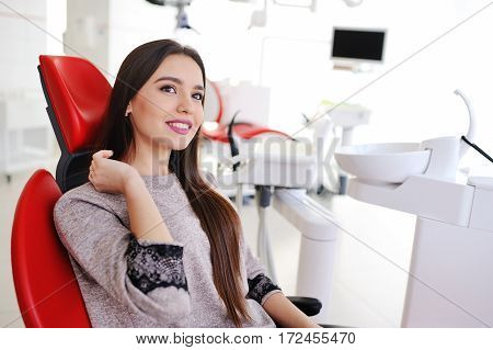 attractive girl in red dental chair at the reception of dentists. Dentistry, teeth whitening, dental fillings, smile, tooth decay.