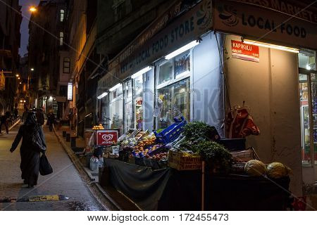 ISTANBUL TURKEY - DECEMBER 28 2015: Food shop on a typical street of Galata in the evening a veiled woman passing by