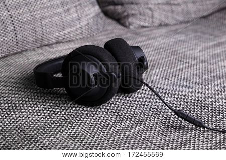 Headphones lying on sofa. Musical concept. Modern device for listening music. Sound earphones on couch.