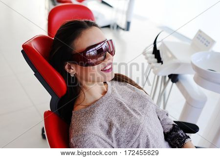 cute young girl patient in dental glasses in red dental chair on a background of a modern clinic
