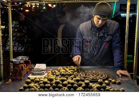 ISTANBUL TURKEY - DECEMBER 28 2015: Picture of an young chestnut seller on a cold winter evening on Istiklal street