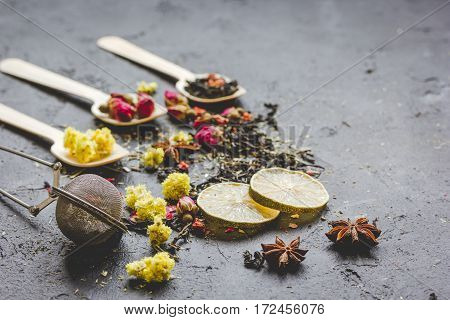 Spoons with herbs on grey stone background
