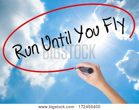 Woman Hand Writing Run Until You Fly  With Black Marker On Visual Screen