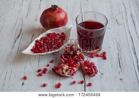 A glass of pomegranate juice, fresh pomegranate grains