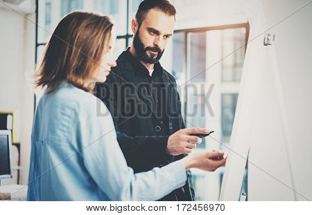 Teamwork and brainstorming concept.Young creative coworkers working with new startup project in modern office.Bearded man writing on the presentation board.Horizontal, blurred background effect