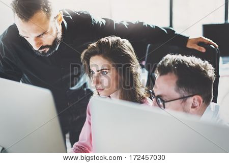 Teamwork concept.Young coworkers working with new business project in modern office.Group of three people analyze data on desktop computer.Horizontal, blurred background