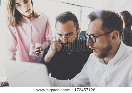 Teamwork process at modern office.Young coworkers team discussing new startup project at meeting room.Blurred background, film effect