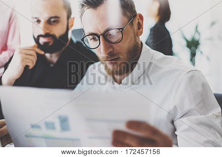Closeup view of two businessmans at modern office.Young coworkers analyze marketing reports at meeting room.Blurred background, horizontal