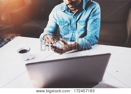 Smiling bearded African businessman using phone while sitting at the wooden table on his modern home.Concept of young people working with mobile devices.Blurred background