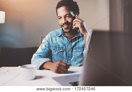 Attractive young African man talking by smartphone while sitting at the wooden table his modern home.Concept of young people working with mobile devices.Blurred background, flares, crop