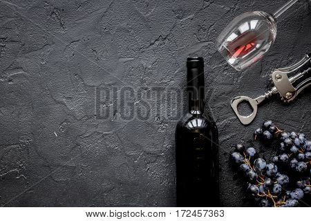 Glasses of red wine and bottle with corkscrew on dark stone background top view mockup