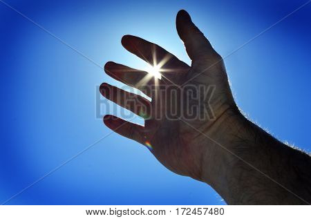Reaching hand to heaven seeking heavenly light