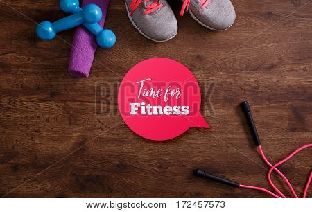 Fitness gym equipment. Sneakers, dumbbells with towel and skipping rope. Time for fitness speech bubble. Grunge rustic wood background.