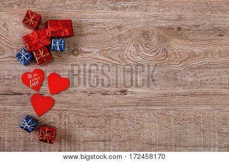 Red hearts and gift boxes. Valentines day or 8 march design. Romantic love on rustic wood background. Wooden grunge board.