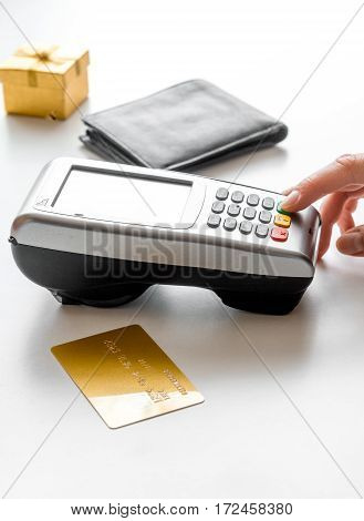 Present in box, wallet and credit card with payment terminal in a shop on white table background