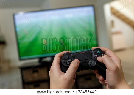 Man playing video game. Hands holding console controller. Football or soccer game on the television. Widescreen tv stands on commode.