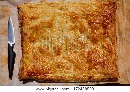 Puff vegratables pastry square shape with knife on oven paper
