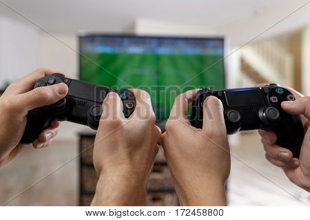 People playing video game. Hands holding console controller. Football or soccer game on the television. Widescreen tv stands on commode.