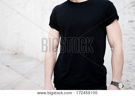 Closeup view of young muscular man wearing black tshirt and jeans posing outside. Empty white wall on the background. Hotizontal mockup