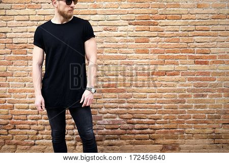 Young muscular man wearing black tshirt, sunglasses and jeans posing outside. Empty brown grunge brick wall on the background. Hotizontal mockup