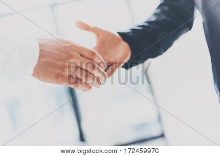 Close up view of business partnership handshake concept.Photo two businessman handshaking process.Successful deal after great meeting.Horizontal, blurred background