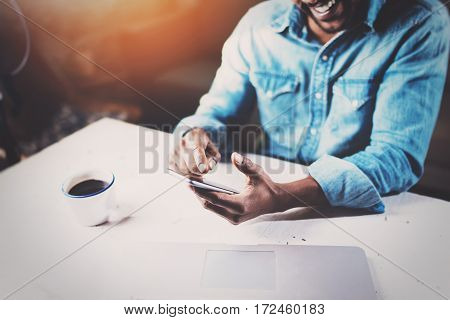 Smiling young African man using smartphone while sitting at the wooden table his modern home.Concept of people working with mobile devices.Selective focus on male hands.Blurred background, flares