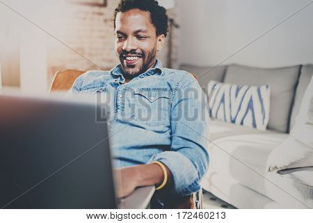 Happy young bearded African man spending rest time at home and using laptop.Concept of people enjoying mobile devices.Blurred background, flares