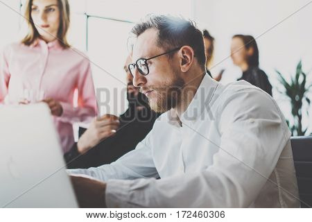 Business team concept.Young professionals discussing new business project in modern office.Group of three people analyze reports on desktop computer.Horizontal, blurred background