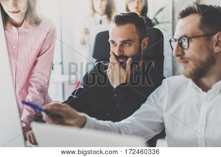 Teamwork concept.Young coworkers discussing new business project in modern office.Group of three people analyze reports on desktop computer.Horizontal, blurred background