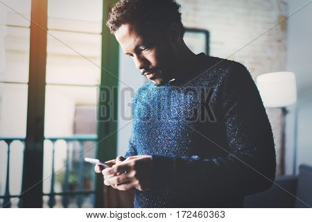 Pensive young African freelancer typing screen of mobile phone while working in new project at home.Black man looking for information on Internet.Blurred, color filter, flares