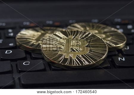 Shiny gold Bitcoin coin laying on black keyboard