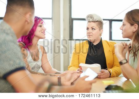Candid picture of a startup business team collaborating on their next design project and using technology. Filtered serie with light flares, bokeh and warm sunny tones.