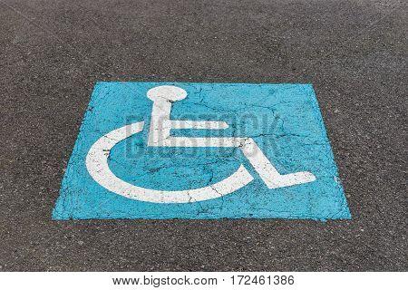 image of sign on the asphalt parking for disabled