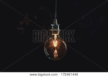 Vintage edison lightbulb with glowing wire on dark background