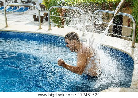 Young handsome man wearing sunglasses enjoying jet of water in the pool and having fun on summer holidays.