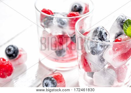 Icecubes with frozen blueberry and raspberry and mint in glass on white wooden table background