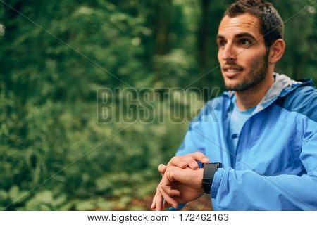 Portrait of a competitive, athletic young man ctracking his performance with an app on smart watch while running off road outdoors through the woods on a trail in the afternoon wearing sportswear.