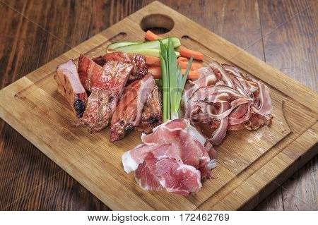 wooden board on the table with smoked beer snacks - ribs pork ears jamon cucumber carrot onion. top view